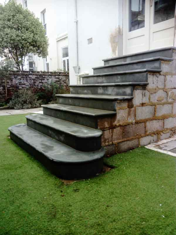 Dark york stone steps leading to garden.